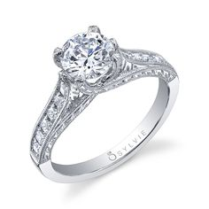 This exquisitely detailed 18K white gold engagement ring includes a channel milgrain setting with hand-engraving down the sides of the shank. Delicate prongs hold the round center. Semi carat weight totals 0.26 (center not included).
