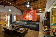 Cobogó separando ambiente da sala, gerando corredor ventilado com portas para rua e quartos.
