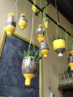 Reciclaje en estado puro, estas jardineras están hechas con botellas plásticas y el tratamiento se reduce a pegar los tapones, pintar las botellas y practicar unos orificios para introducir las cuerdas.