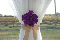 Pop of purple on tulle curtains with a country burlap bow. Simple and sweet!