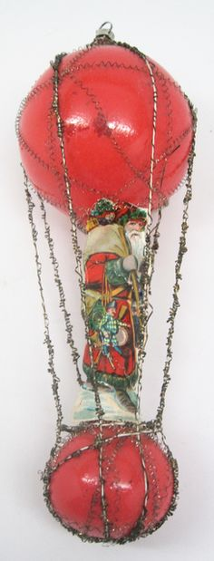 Victorian wire wrap Christmas ornament made of red blown glass and decorated with tinsel wire from top to bottom. A paper scrap full length picture of Santa with a large bag of toys is attached at the center. Manufacturer unknown, circa 1890.  Collections Online : mnhs.org