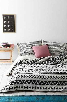 Black & White Graphic Patterned Bedspread & Pillow Covers, White Painted Floors, Bright Teal Rug // design