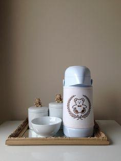 Kit higiene cappuccino composto por bandeja 33,5×22,5 cm com fundo em espelho, 2 potinhos com 8 e 10cm e molhadeira 11,5×5,5cm em porcelana branca com aplique de ursinho decorativo em resina e garrafa térmica Termolar 500ml com capa em linho bordado. Pode ser feito em outras cores sob consulta.