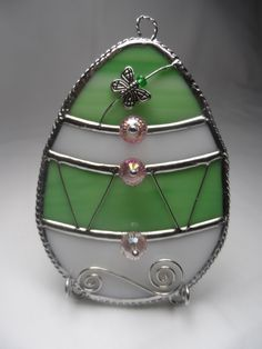 """Stained Glass Easter Egg in Green and White with Pink Cut Glass Beads, sort of a retro / vintage style. Egg is 4"""" high and 3"""" wide. Comes with tripod wire stand or hanging chain. At Jitter Beans in Mineral Wells, Texas"""