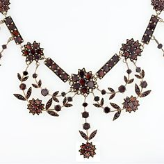 This early 20th century necklace is made in the Bohemian garnet style of the late 1800's. It is studded with glowing orangy red garnets and draped in festoons of floral garlands. The garnets are set in rose gilded base metal.