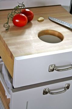 Cutting board drawer with a hole over garbage drawer. Very smart!
