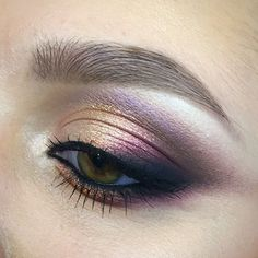 Gold eyeshadow on the eyelid and taupe smudged into the crease. Black and cranberry shades darken the outer corner of the eye.