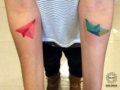 Geometric watercolor paper airplane and boat forearm tattoo.