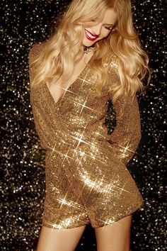 As Seen On Laura of The Band Wife blog! Have your outfit shine as bright as your personality in the Good as Gild Gold Sequin Romper! Bright gold sequins sparkle over this long sleeve romper with a surplice bodice that secures with a single snap below the deep V neckline. Long sleeves have fitted cuffs. Elastic waistband.