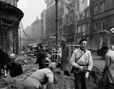 The famed Unter Den Linden in Berlin is badly damaged by aerial bombing and shelling. Civilians work under direction of Russian soldiers to clear rubble away for pedestrian and motor traffic. May 4, 1945. Stock Photo - Corbis