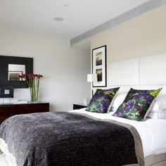 Modern bedroom with white leather bed and velvet bedspread