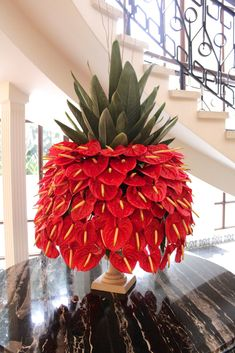 Could symbolize food, in a zombie apocalypse food is abundant and this arrangement looks like a pineapple but red. There will be 3 tables, the two outside tables will have yellow anthuriums and the center will be dark red. Exotic Flowers, Tropical Flowers, Beautiful Flowers, Silk Flowers, Tropical Flower Arrangements, Church Flower Arrangements, Jeff Leatham, Hotel Flowers, Corporate Flowers