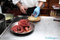 preparando una tabla de pulpo a la gallega en el stand del centro gallego de la region de murcia