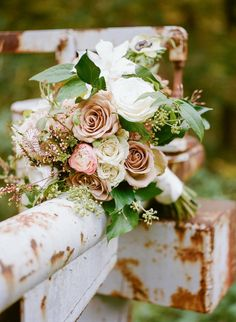 Old, rusty, pipe fence makes a perfect backdrop for this bouquet ❤