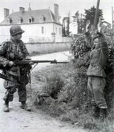 Un soldado estadounidense apunta cunha arma a un soldado alemán.