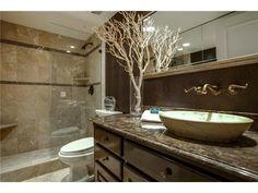 Oval vessel sink // Rich wood vanity // Open glass shower