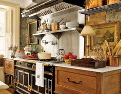 Adore this kitchen , complete with a fabulous La Cornue, reclaimed cabinets...copper, art... love lamps in kitchens...perfect cottage kitchen. Love!