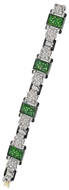An Art Deco carved jade and diamond bracelet, 1920s. Featuring four pierced jadeite plaques framed by four larger marquise-shaped diamonds weighing approximately 1.20 total carats and 256-round diamonds weighing approximately 7.70 total carats, with black enamel accents, mounted in platinum. #ArtDeco #bracelet