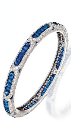 *PLATINUM, SAPPHIRE AND DIAMOND BANGLE-BRACELET, BOUCHERON, PARIS, CIRCA 1920 The hinged bangle centering upon a line of calibré-cut sapphires within diamond-set crossover borders, the sides enhanced by rose-cut diamonds punctuated by modified triangular-shaped sapphires, TDW approx 5.50 carats, signed Boucheron, Paris, French assay marks Www.ambragold.Com