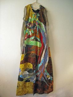 """Lorie McCown earthdress  An art dress. Hand dyed silk, cotton and linen fabics. Over dyed gauze and reused laces. Hand and machine stitched, quilted and embroidered. Hand made hanger. 70"""" long."""