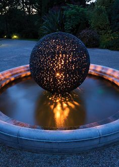 A tantalising, perfect garden sphere of black puddle stones, washed smooth by centuries of gentle erosion in river water by David Harber