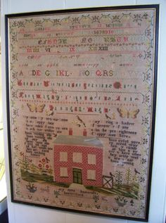 """A Charming and unusually large Sampler by Mary Emma Wheatcroft of Chesterfield, England, dated 1875, in good fresh condition with slight wear & tear commensurate with age.  Close-ups of the latter are shown on the website.  Above the happy verses of text, amongst the delightful birds, flowers, trees and butterflies surrounding the house, are the beautifully detailed letters of the alphabet and numerals, all surrounded by the prettiest of patterned borders. 26"""" x 35"""" NOW SOLD!"""