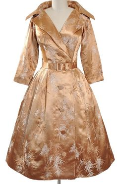 1950's party dress made of golden silk brocade with a beautiful iridescent shimmer. Features a wide spread portrait collar on the bodice with a dramatic rounded cape style back collar, a plunging v-neckline, front wrap closure, fabric covered button, three-quarter length sleeves, matching belt, and a full swing skirt. Made by Alfred Shaheen.