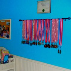This curtain rod on the wall is a neat way to display sports medals.