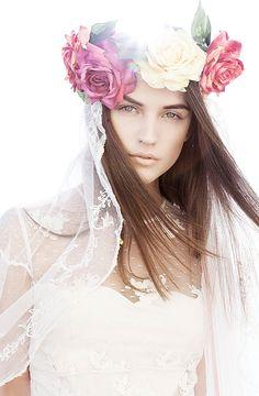 Uma noiva versão princesa prometida. Delicada, elegante, leve. De branco e com suas botas e uma coroa de flores no cabelo. Seu look de noiva boho, um vestido de noiva com as costas descobertas, unhas pintadas de preto.