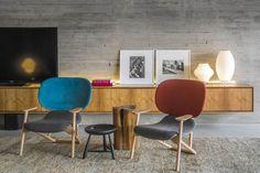 revêtement mural aspect bois grisâtre dans le salon avec meuble de rangement en bois et chaises en bois avec tapisserie bleue/rouge