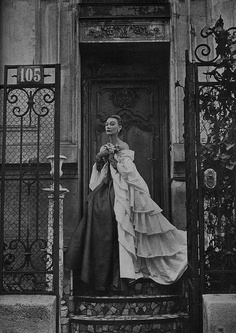 By Hubert de Givenchy;   Off the shoulders and ruffled to the ground, a cape of white shirting trailing over a charcoal organza dress that's tied at the waist with streamers of crimson ribbon. Harpers Bazaar April 1952