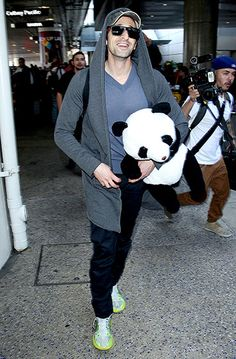Clutching a giant panda doll, Adrien Brody touched down at LAX Airport in Los Angeles Feb. 16.