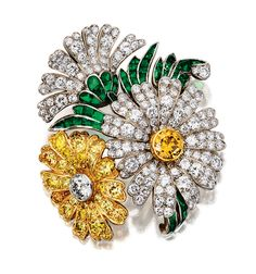 EMERALD AND DIAMOND BROOCH.   Designed as a spray of daisies, set with circular-, brilliant- and single-cut diamonds, some of yellow tint, and calibré-cut emeralds, mounted in yellow gold and platinum.
