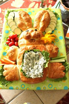 Easter bunny filled with spinach artichoke cream cheese dip in its belly with carrots cucumbers and tomatoes