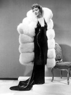 Claudette Colbert, 1935, in a Travis Banton gown and an enormous white fox fur coat