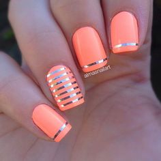 Neon orange matte colored nails with hints of silver metallic strips added on top for effect.