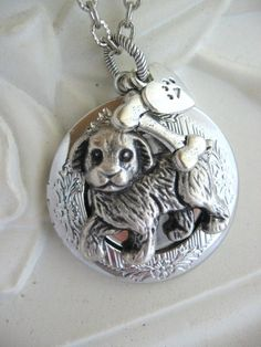Sparky    This whimsical locket necklace features a darling puppy dog with great detailing. The dog is a repurpossed vintage button. It is
