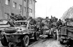 A VW Type 166 Schwimmwagen along with soldiers in various other vehucles surrendering to American forces in the last days of WW2 in Europe