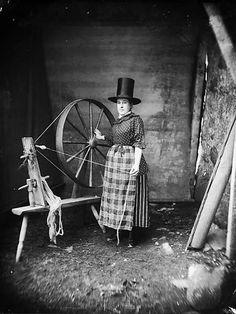 Welsh woman in traditional dress, at her spinning wheel // circa 1885