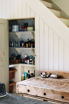 "Kitchen design by Plain English from the UK's House & Garden, ""All our food is stored in this beautifully designed walk-in larder, which contains a honed Carrara marble worktop and shelves alongside practical details, such as a wine rack and space for baskets."""