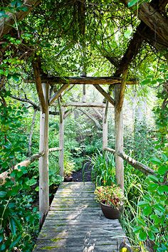 This garden bridge, built with cedar poles, has a rustic wood canopy with akebia vines forming a green roof.