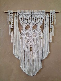 Macrame Wall Hanging Tapestry This fabulous layered Bohemian Macrame Wall Hanging is a smaller version of one of my best sellers. It is wonderfully layered and includes brass tubes and beading. It is truly beautiful. This is modern macrame at its best. This would fit in any area of your home. It can grace your living room, hallway, bedroom or anywhere else you want the ordinary transformed into stunning.  Original design and crafted by Lucy Lanuza    Made of: Soft cotton rope Soft...