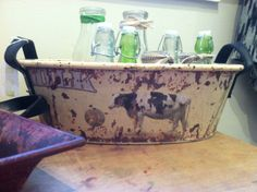 Distressed tub with cow image filled with vintage milk bottles.
