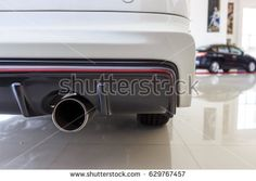 closeup exhaust pipe of a car with soft-focus in the background. over light