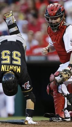 Cincinnati Reds catcher Ryan Hanigan, right, watches as Pittsburgh Pirates' Russell Martin (55) spins around after being hit by a pitch from starting pitcher Bronson Arroyo in the fifth inning of a baseball game on Wednesday, June 19, 2013, in Cincinnati. (AP Photo/Al Behrman)