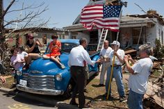 The President visited Joplin, Missouri, following a devastating tornado. Here he greets Hugh Hills, 85, in front of his home. Hills told the President he hid in a closet during the tornado, which destroyed the second floor and half the first floor of his house. Photographed on May 29, 2011