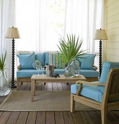 This beach style living space could be used indoors or out. Sisal rug, aqua furnishings and accents of natural palm fronds in clear glass vessels. Classic simplicity!!!