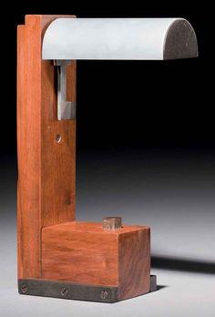 JACQUES LE CHEVALLIER (1896-1987) ET RENÉ KOECHLIN (1866-1951) LAMPE LISEUSE 'N.3', VERS 1928 En noyer, aluminium et ébonite, le réflecteur semi cylindrique orientable, fixé sur un montant latéral de section rectangulaire, la base rectangulaire flanquée de deux tiges d'ébonite Hauteur : 28 cm. Signée du cartouche de l'artiste 'TYPE 3, JLC, R, K' au dos du montant vers la base
