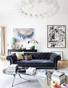 This eclectic Parisian pad features a gorgeous midnight blue velvet chesterfield sofa with a mirrored coffee table, featuring modern art.