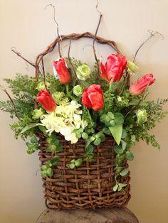 Custom floral arrangement spring door hanger in wooden basket with branch sticks, tulips, hydrangea, periwinkle and maiden hair fern greenery.